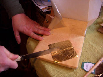 Sheet of gold leaf being put in place
