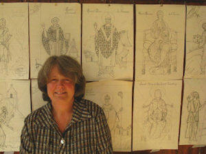 Karen Blampied standing before drawings of Parish Icons